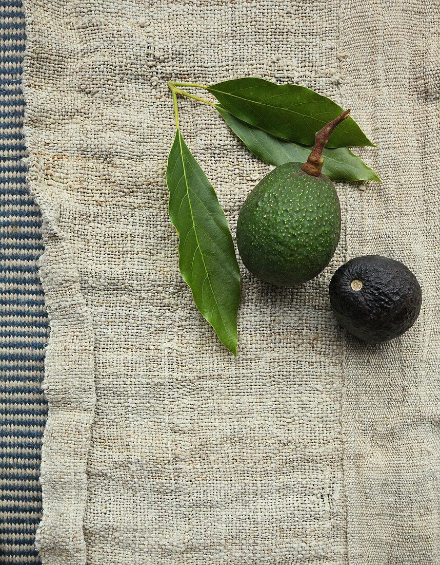 Green and black avocado on a linen cloth