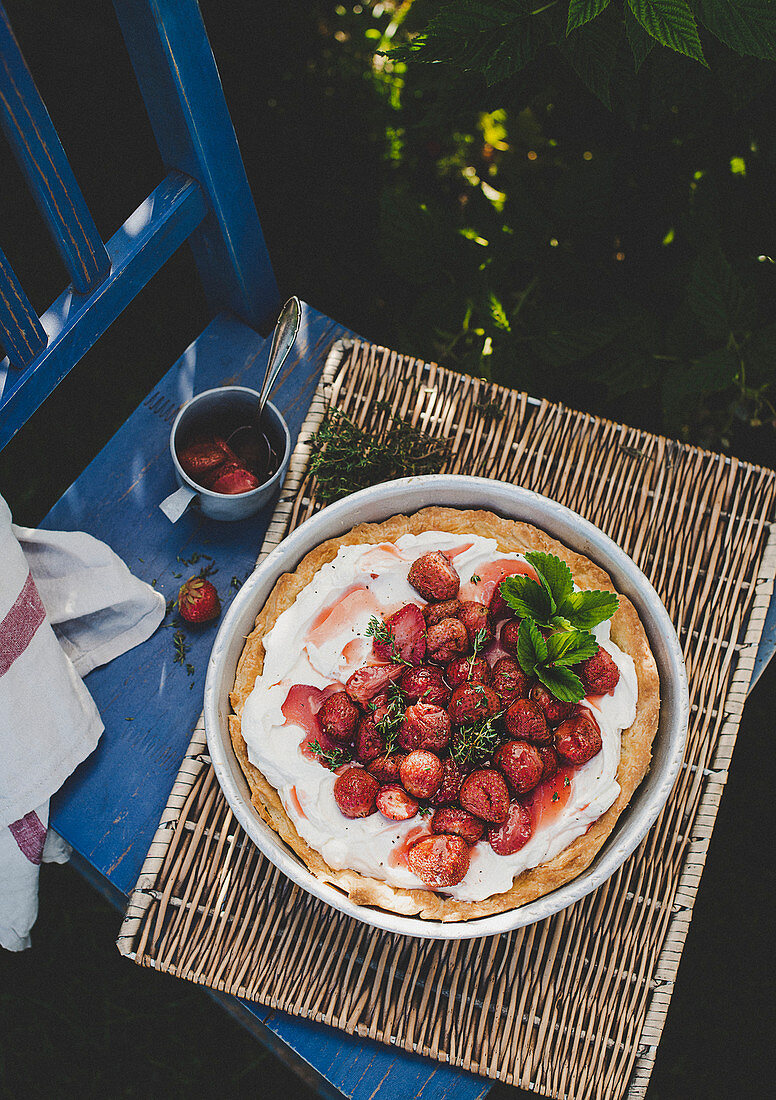 Pie with baked strawberries on a chair in a garden