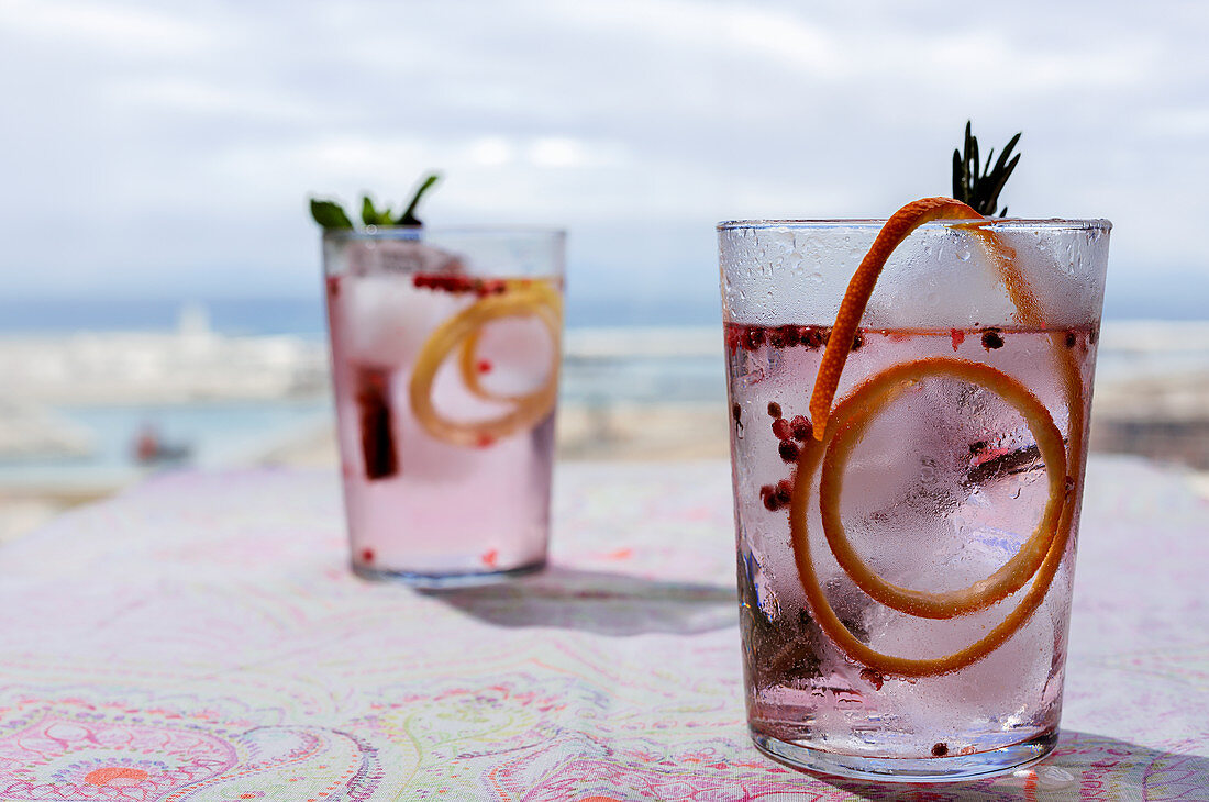 Gin tonic cocktail with pink tonic water, pink pepper, rosemary, mint, cinnamon, lemon and orange in the sunlight on a restaurant table