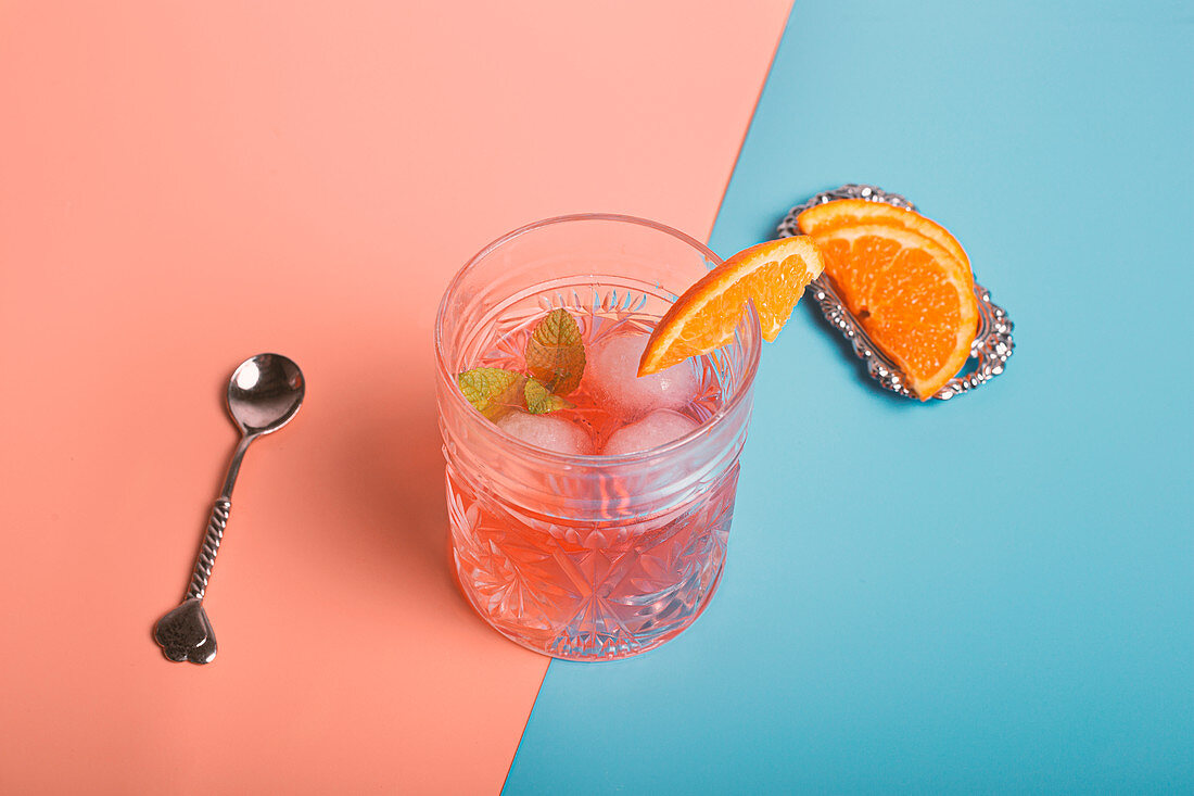 Top view of alcohol cocktail with ice cubes and sprig of mint in glass placed on colorful background with orange slices