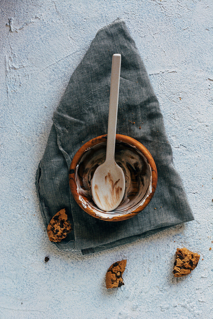 From above pieces of yummy oatmeal cookies placed on plaster surface near cloth napkin and empty bowl with stains of ice cream and spoon