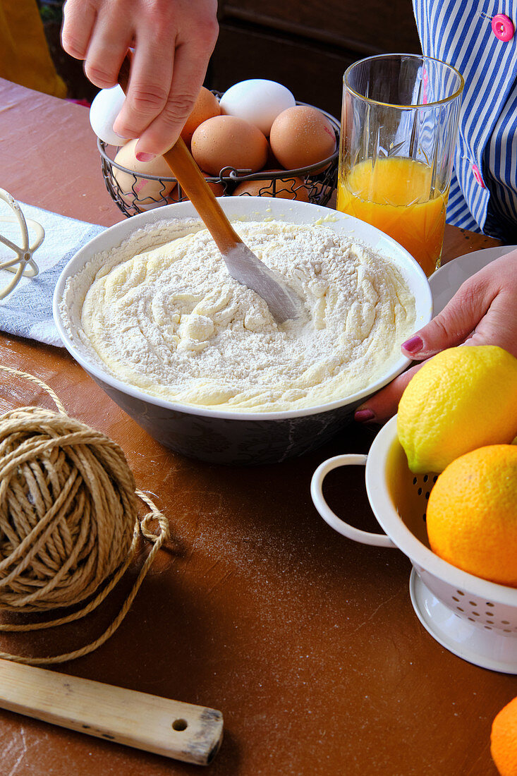 From above anonymous woman using wooden spatula to mix pastry batter near eggs and citrus juice on kitchen table