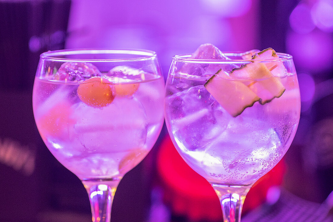 Closeup of glasses with fresh alcoholic tonic cocktail with ice cubes and fruits served against blurred neon background during night party
