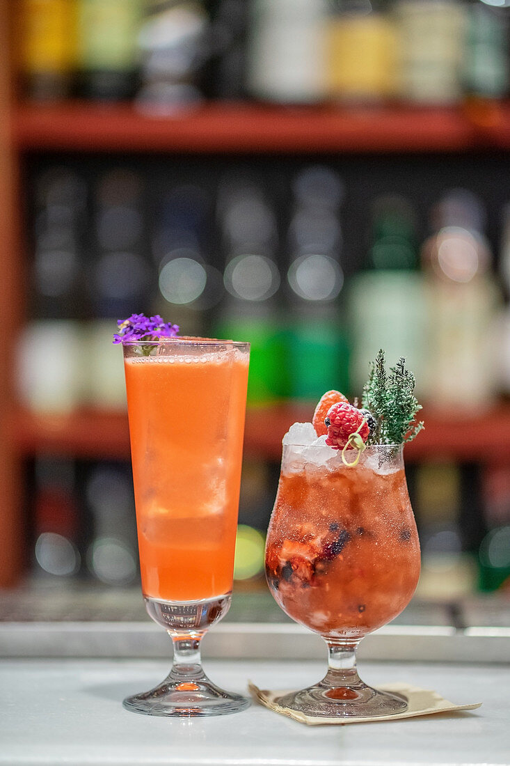 two berry cocktails with ice and fresh herbs at bar counter