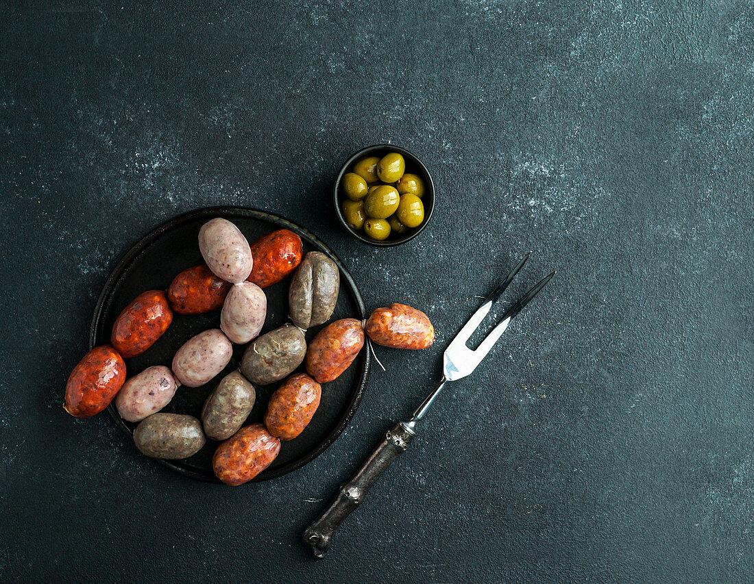 Spanish sausages on the cutting board - butifarra blanca, chorizo, morcilla de cebolla