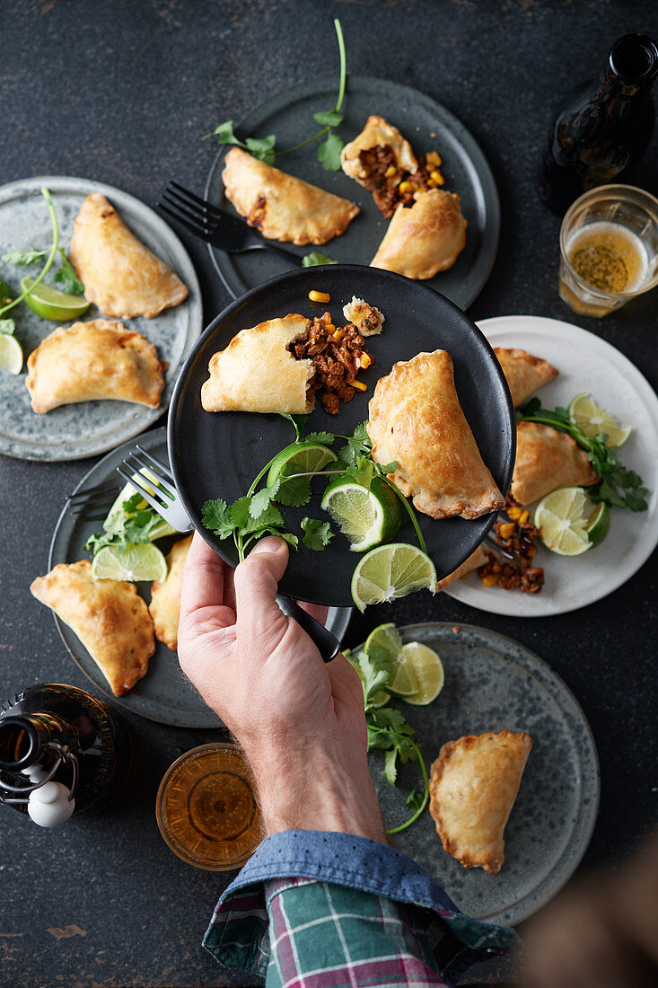 Empanadas with an onion and beef filling, limes and coriander