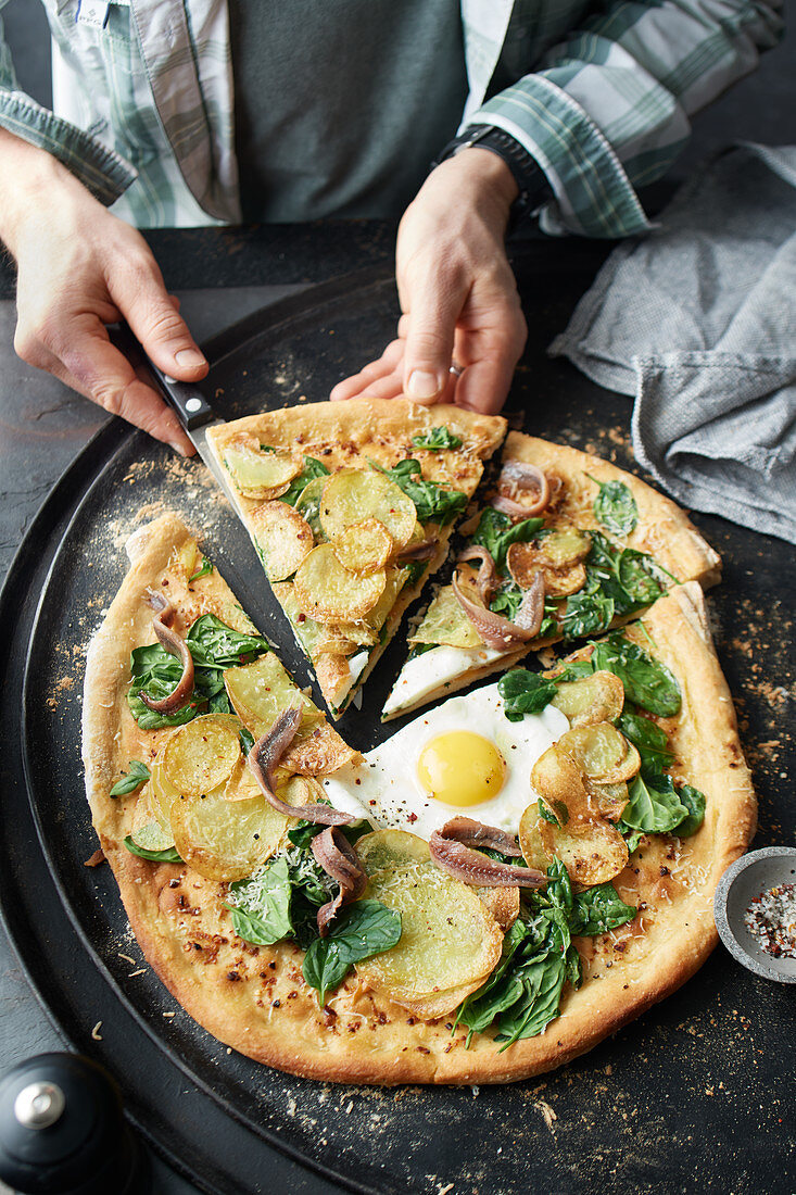 Potato and spinach pizza with anchovies and a fried egg