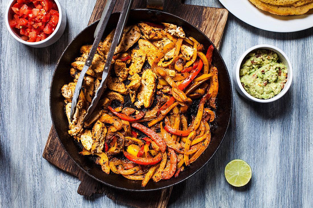 Chicken fajita filling with guacamole and tomato salsa