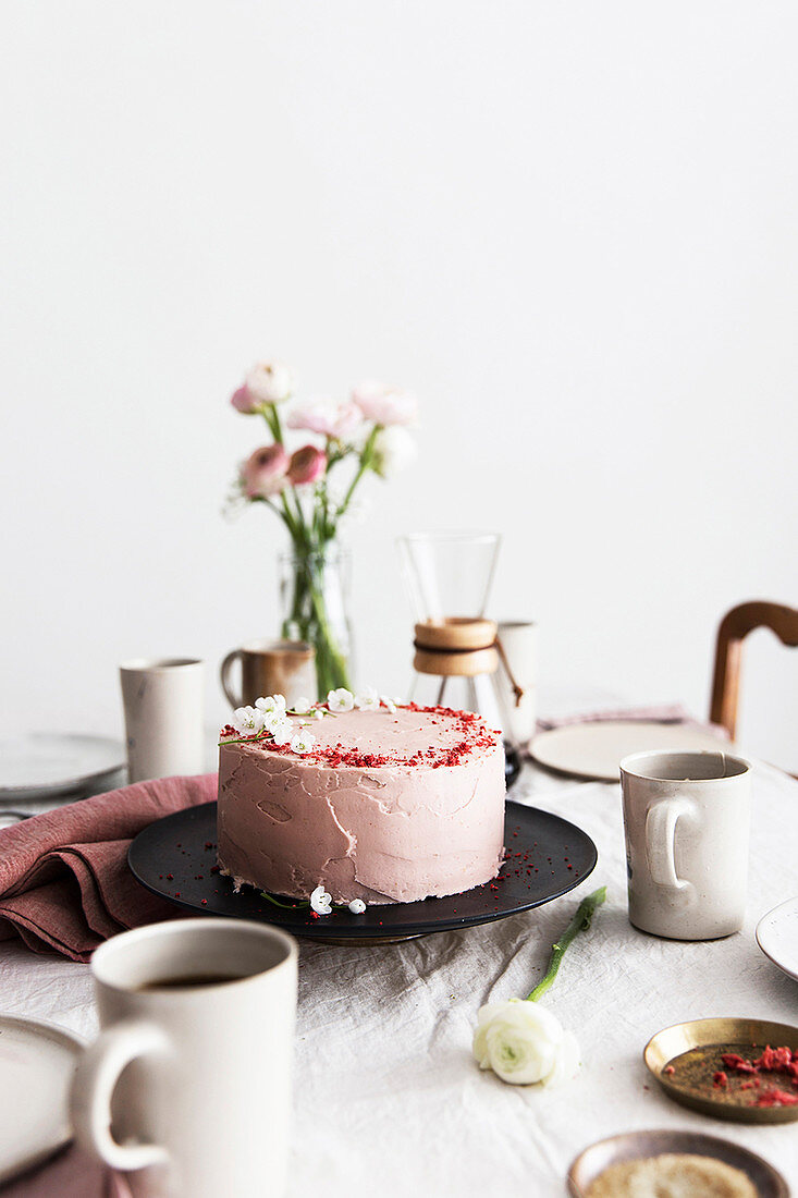 A strawberry cream cake on table laid for coffee