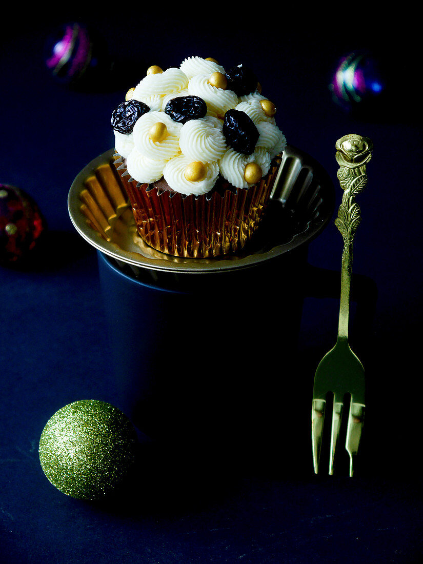 A Christmas cupcake with buttercream and cranberries