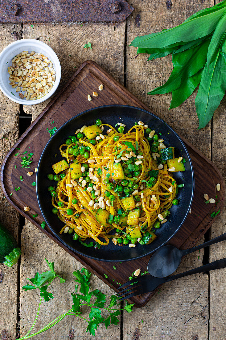 Pasta in spiced butter with zucchini, peas and pine nuts