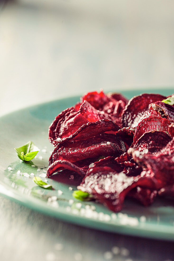 Beet chips with basil and sea salt, on blue plate