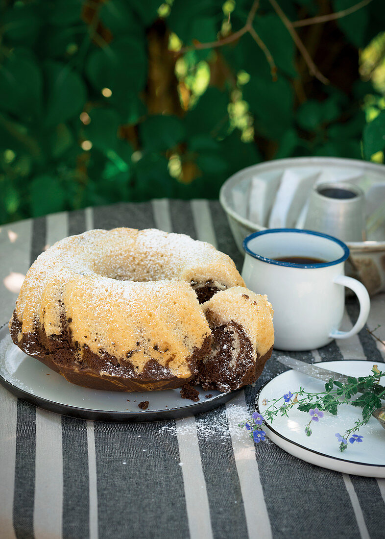 Vegan marble Bundt cake on a table laid for coffee in a garden