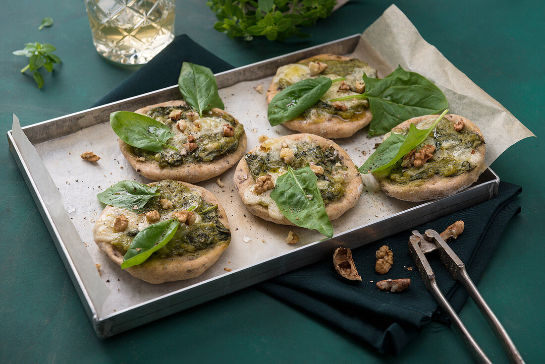 Mini spelt pizzas with spinach, vegan cheese and walnuts