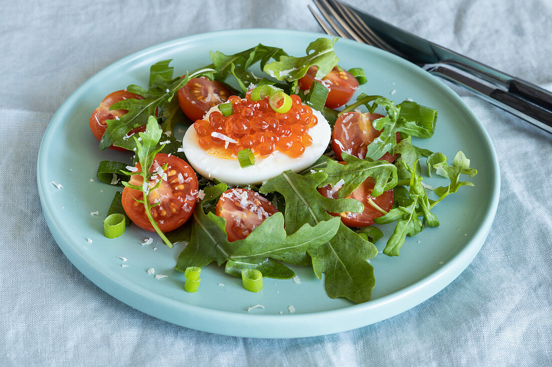 Salad made with arugula, tomatoes, egg, red salmon caviar and parmesan cheese