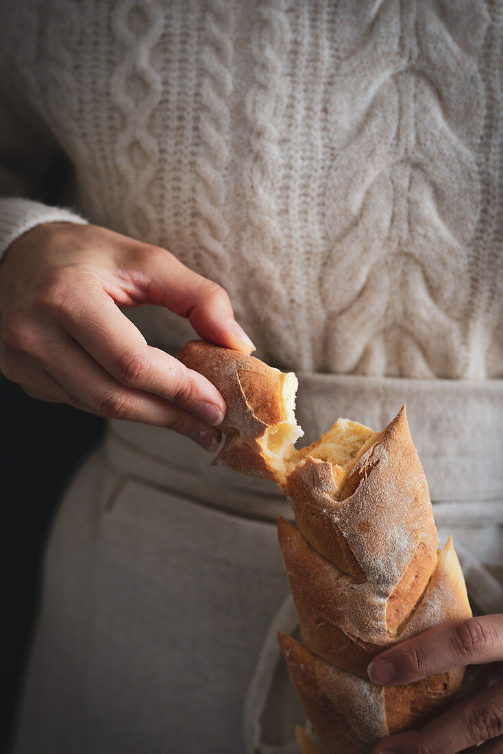 The woman holds a baguette in her hands