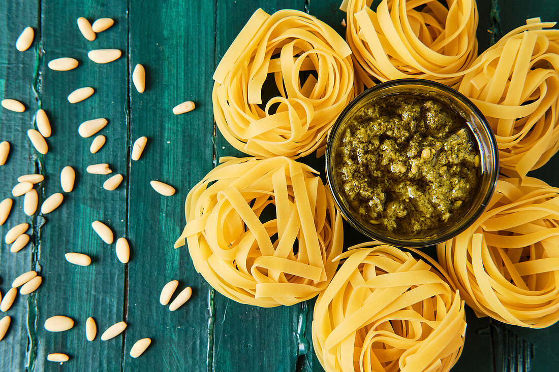 Pesto salsa with olive oil surrounded by uncooked pasta rolls and spilled crunchy pine nuts