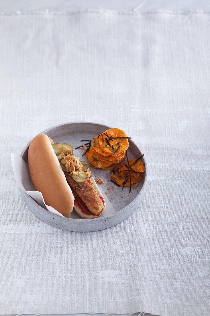 A hot dog with an algae sausage with sweet potato crisps