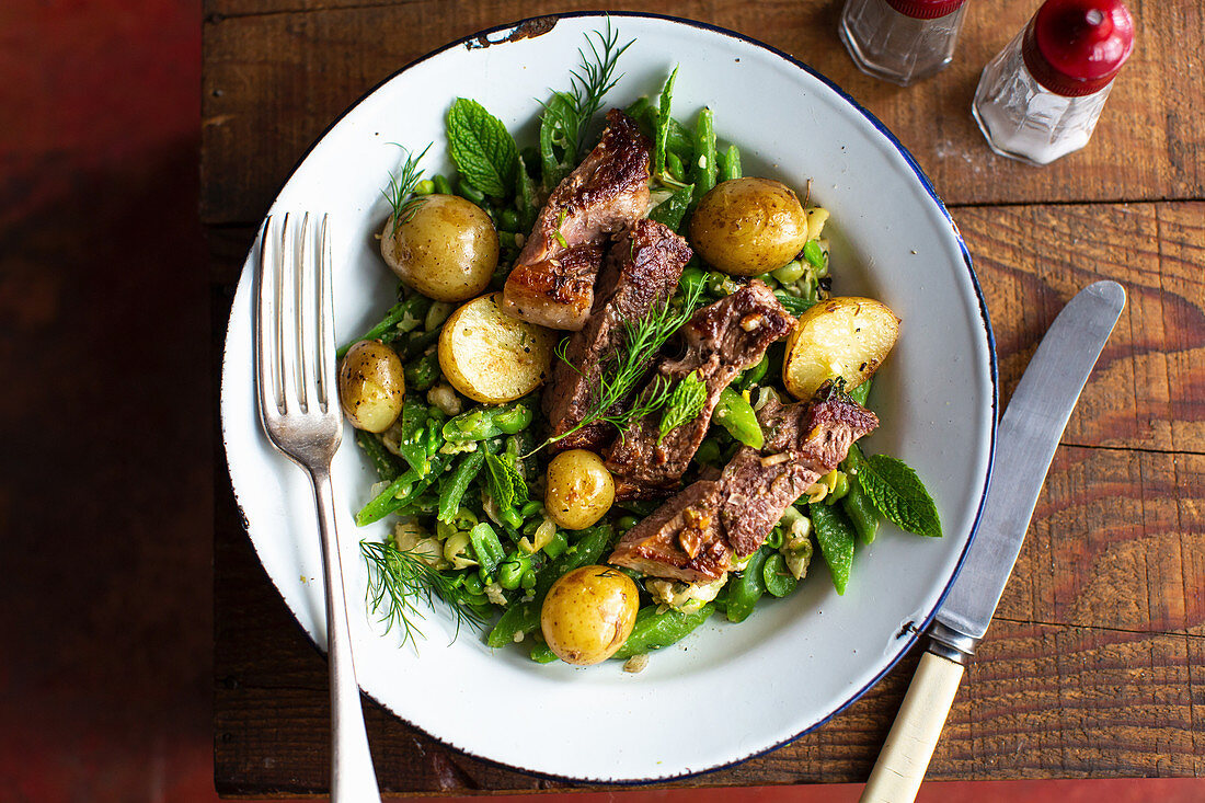 Roasted lamb on a bean salad with new potatoes