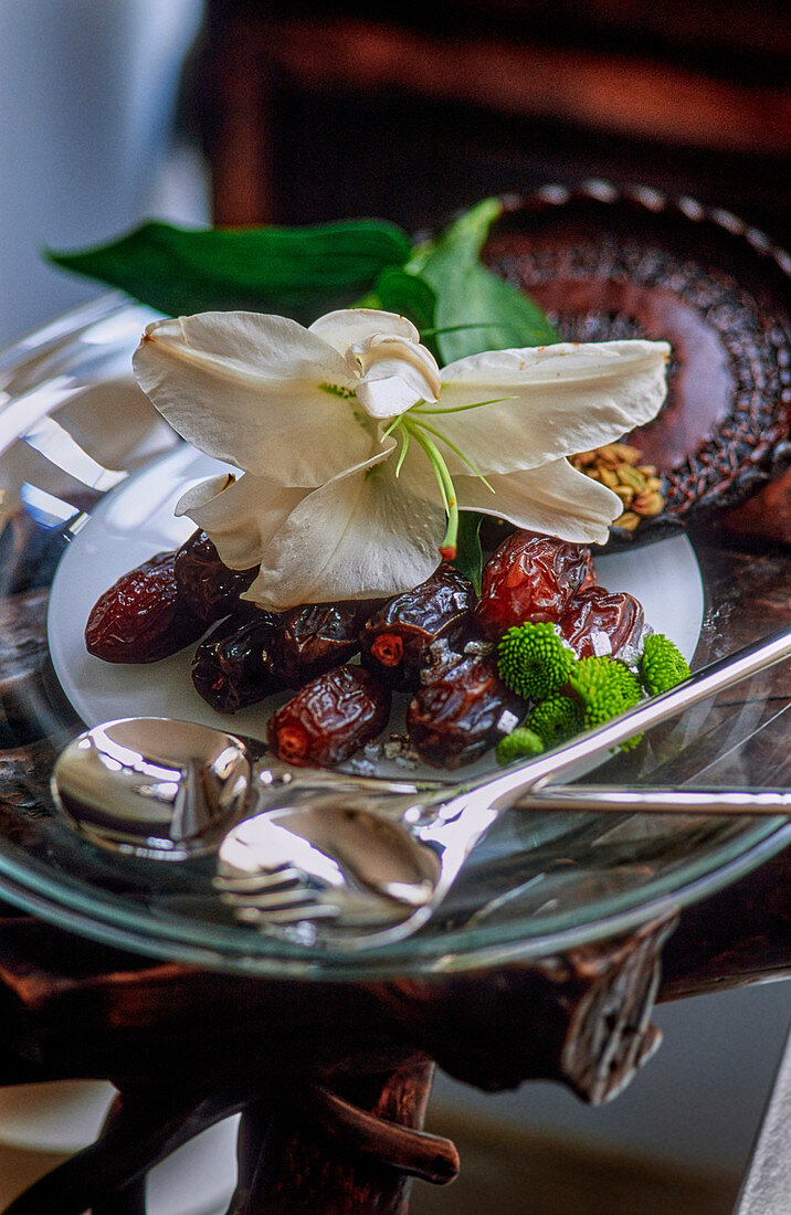 Dried dates with a flower garnish on a glass plate