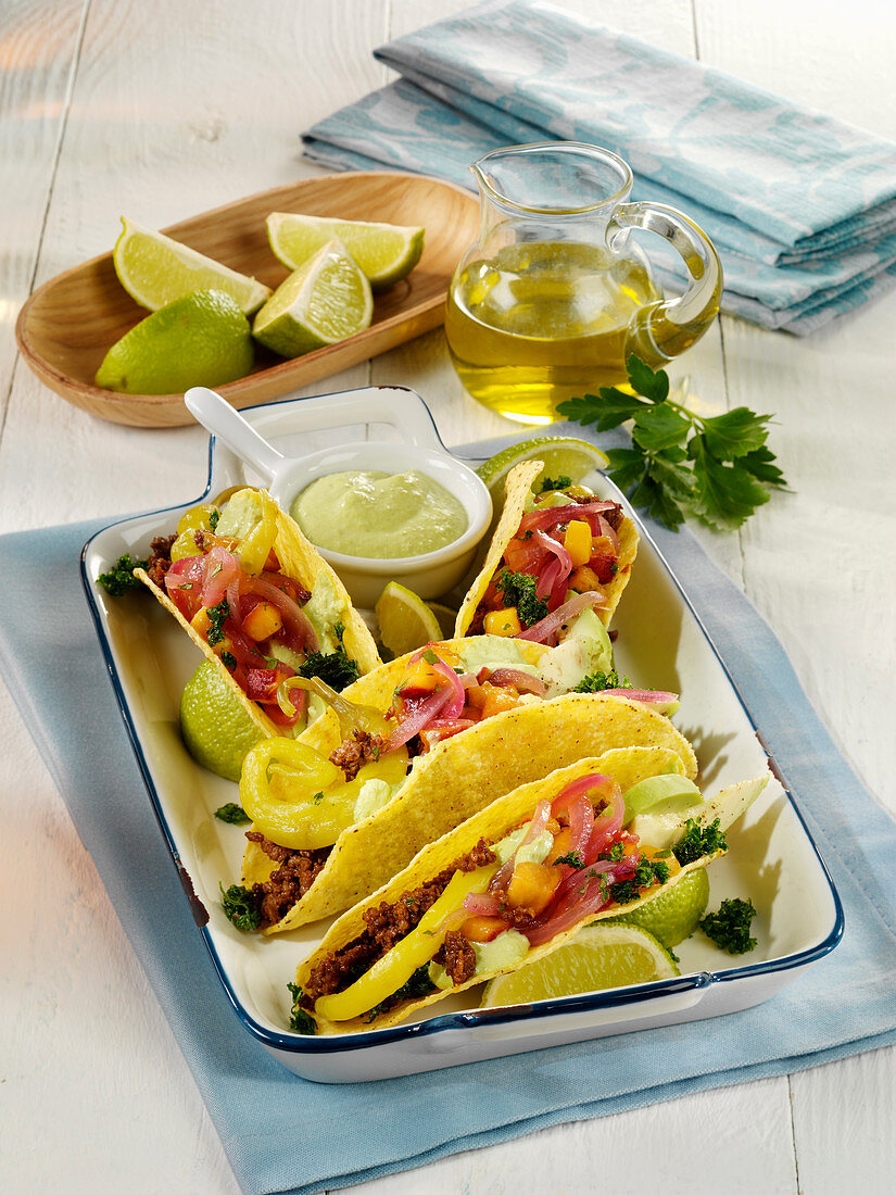 Tacos with minced meat, avocado and mushy peas