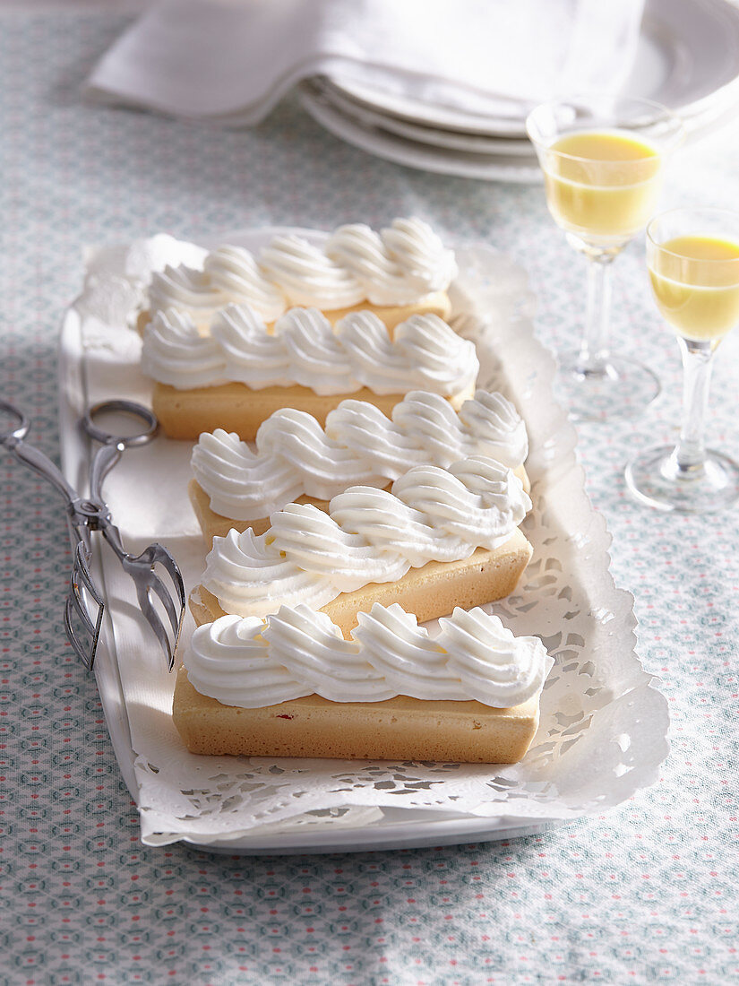 Dessert slices with cream served with eggnog in a glass