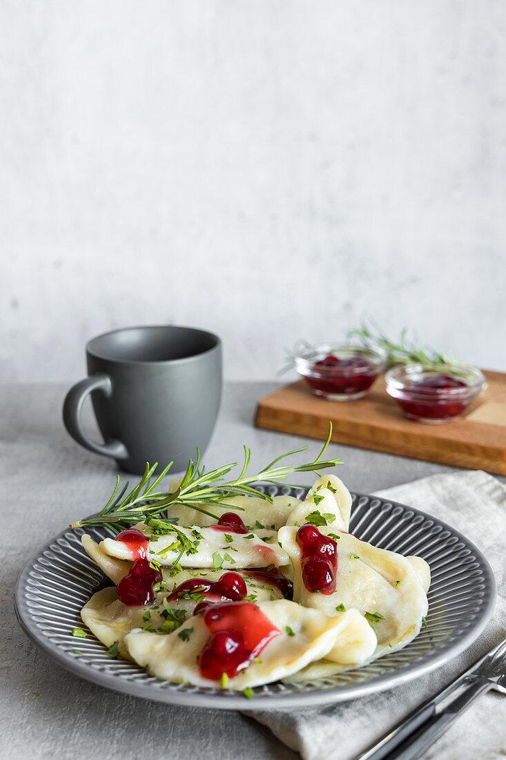 Goose pierogi with cranberry sauce and rosemary