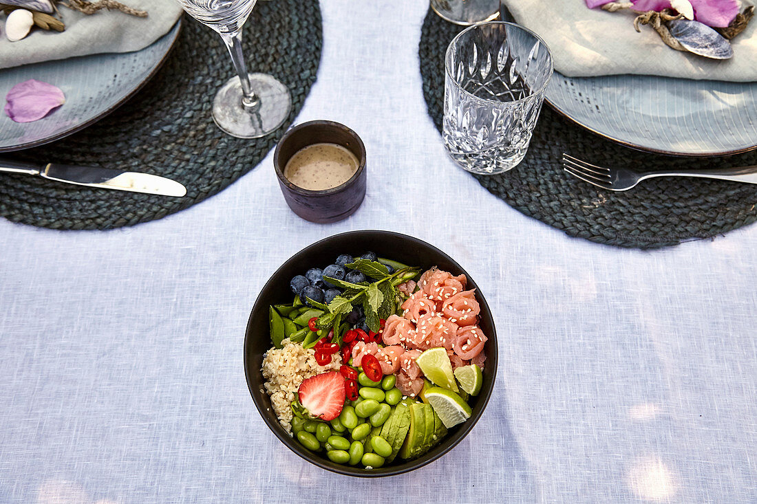 Poke bowl with salmon rolls, edamame and blueberries