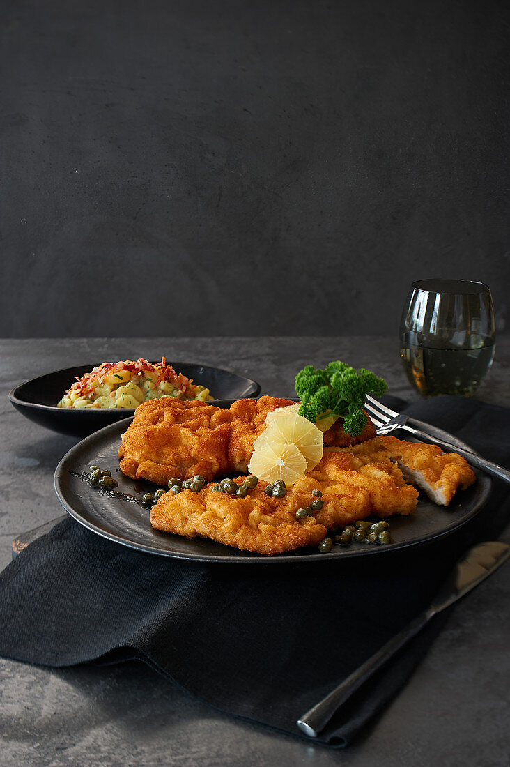 Wiener Schnitzel with caper butter and bacon and potato salad