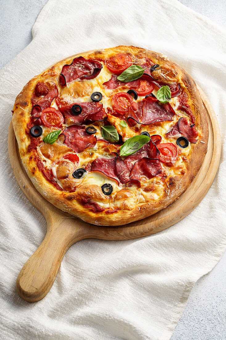 Pizza with prosciutto crudo and olives