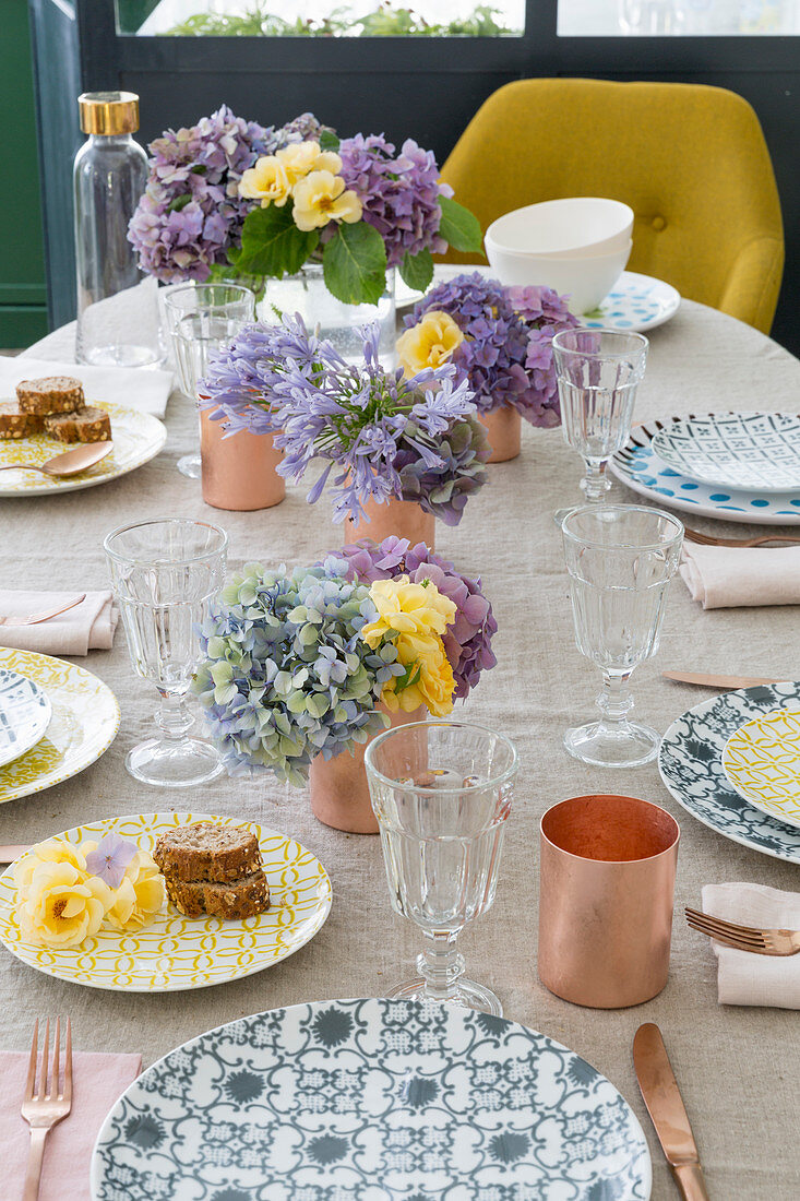 Patterned plates and flowers on table set for summer meal