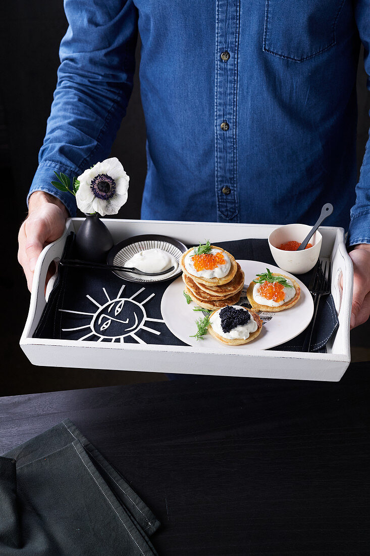 Blinis with caviar and sour cream served on tray