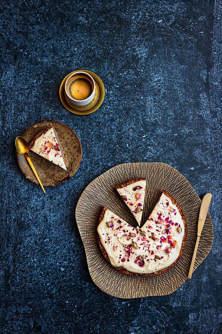 Gluten-free carrot cake with tahini glaze and rose petal decoration
