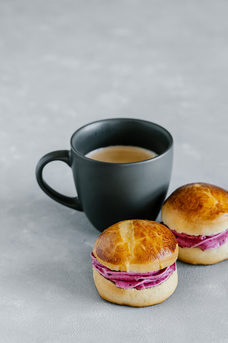 Cup of coffee and brioche buns with blackcurrant cream