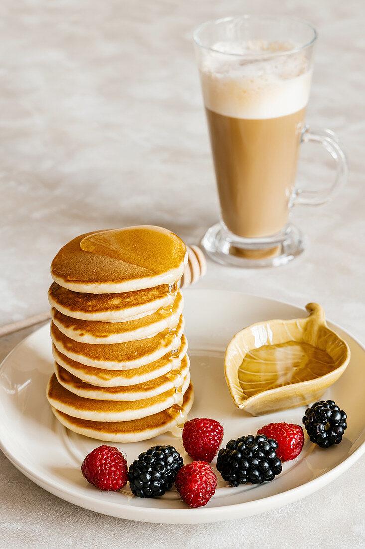 Pancakes with honey, raspberries, blackberries and coffee latte