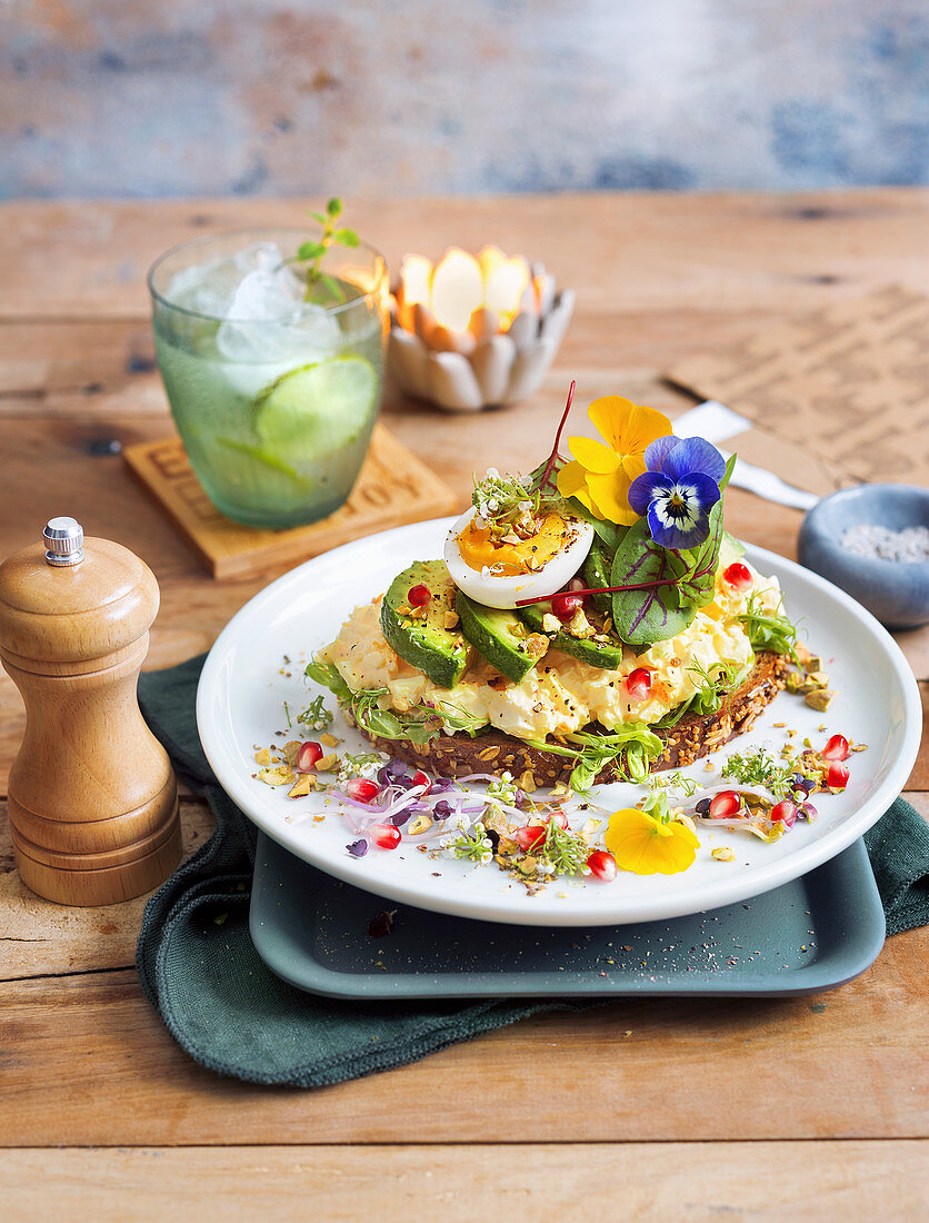 Avocado and egg toast garnished with edible flowers