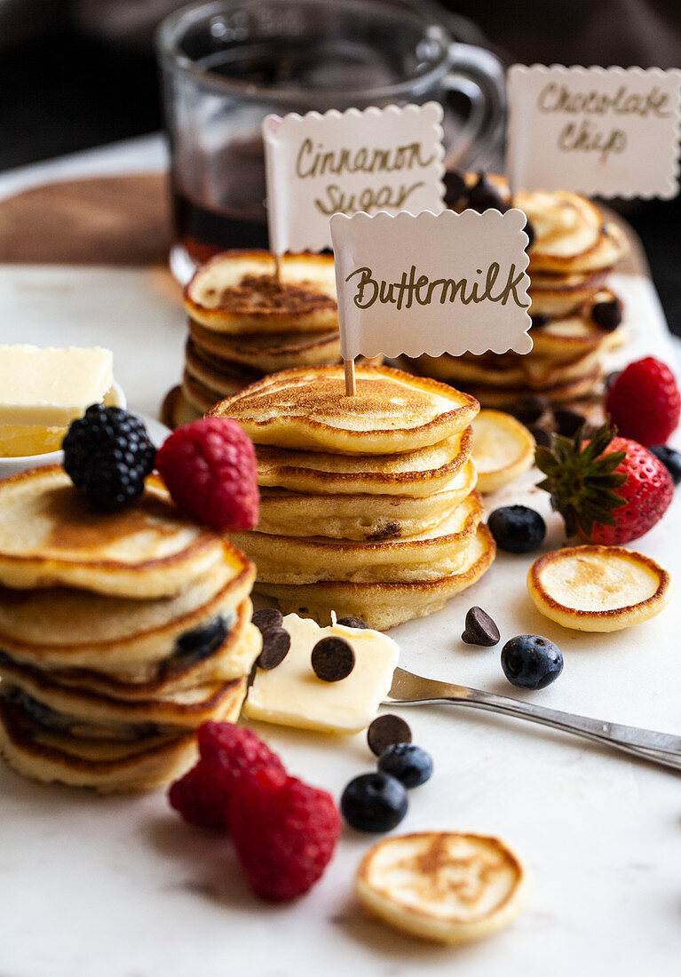 Stacks of mini pancakes with signs, with fruit and chocolate chips, syrup and butter, on a marble board