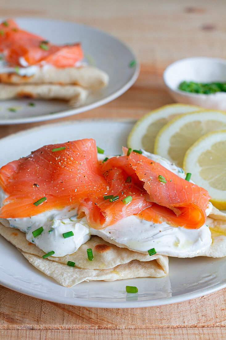 Fatbread pieces with sour cream and salmon fillet garnished with chopped green onion
