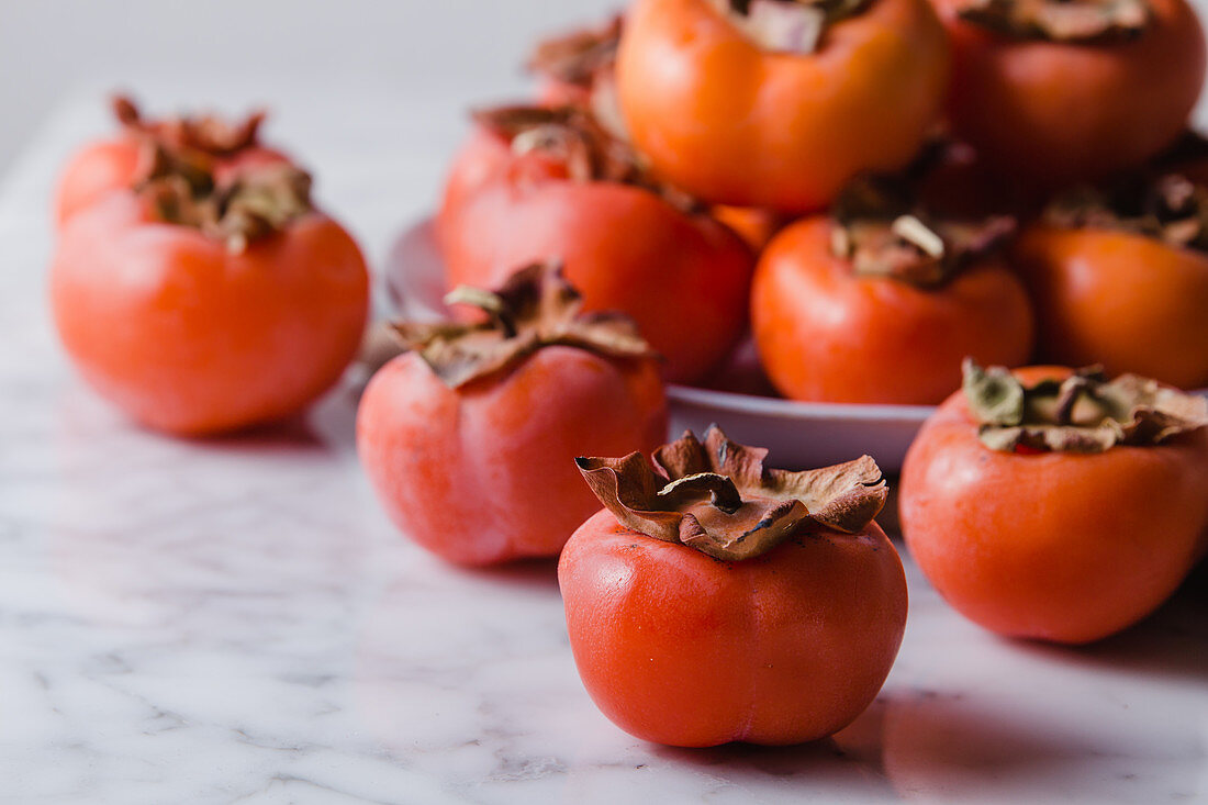 Pile of fresh persimmons on plate placed on white table