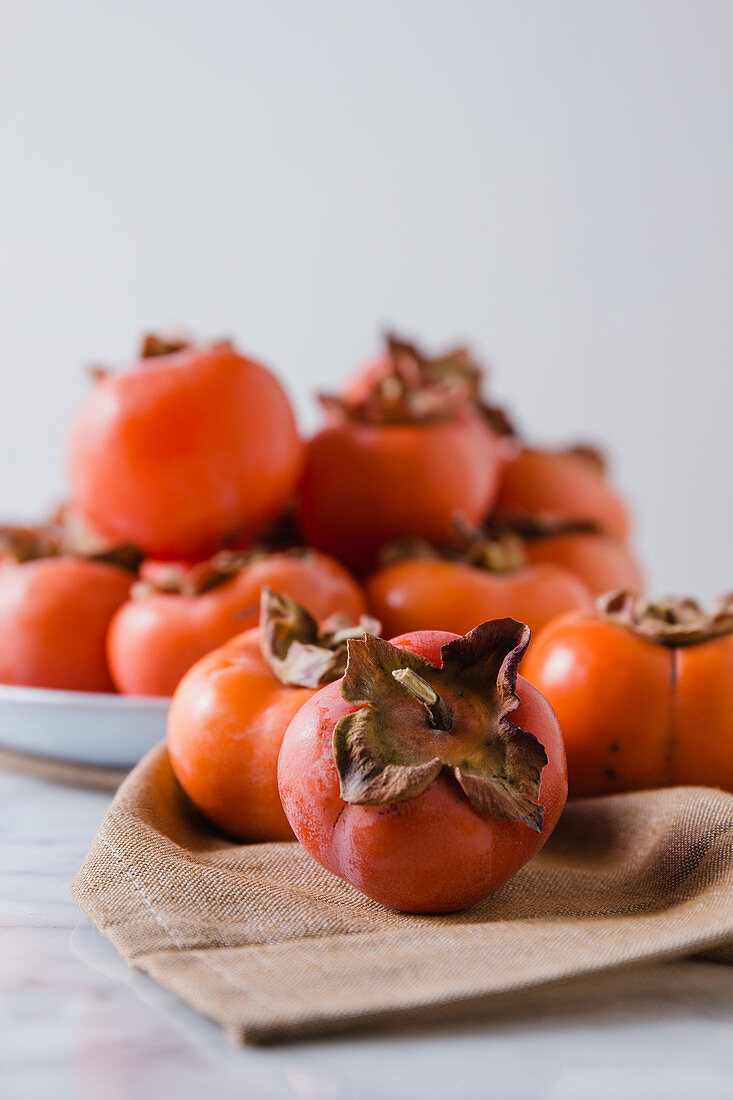 Fresh persimmons on plate placed on white table