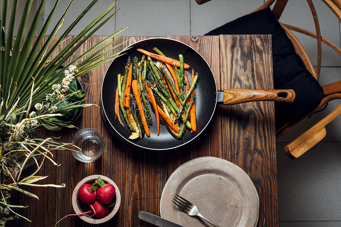 Carrot, asparagus and zucchini sauteed in the pan, on the table ready to eat