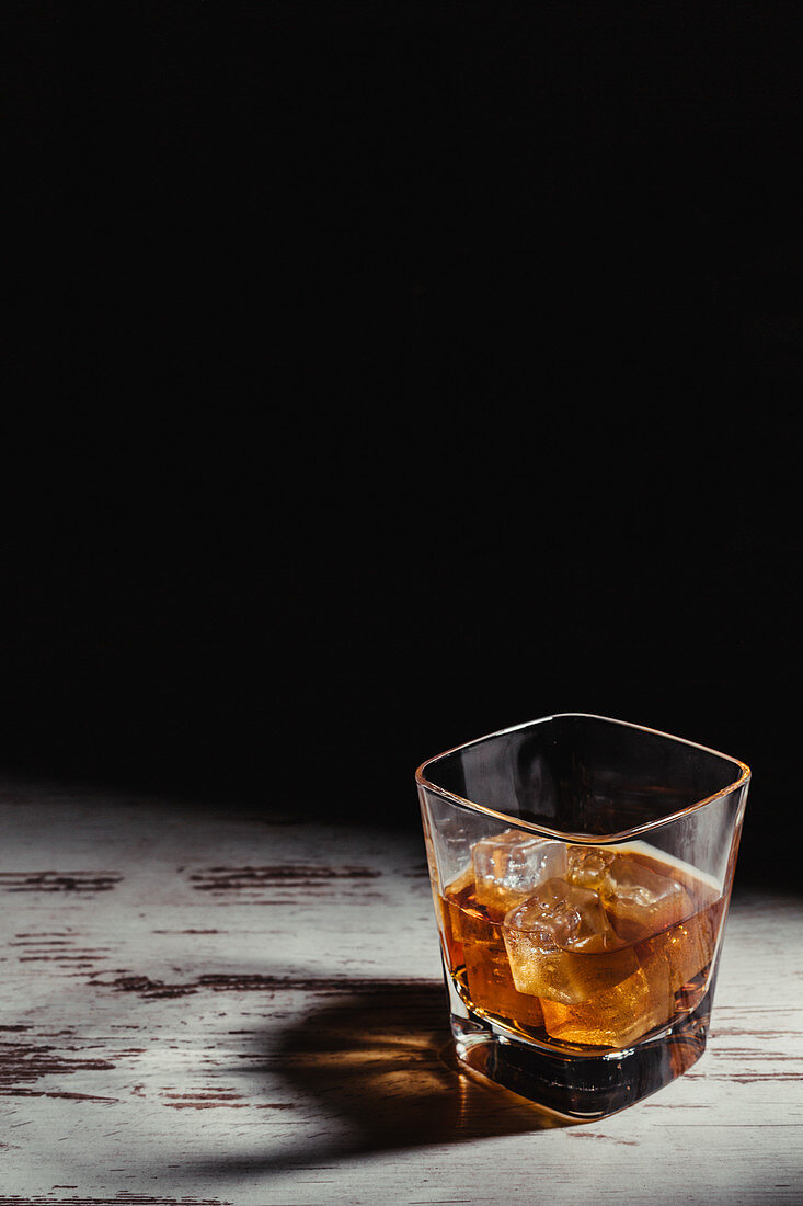 Glass of scotch in rays on aged rustic table in darkness