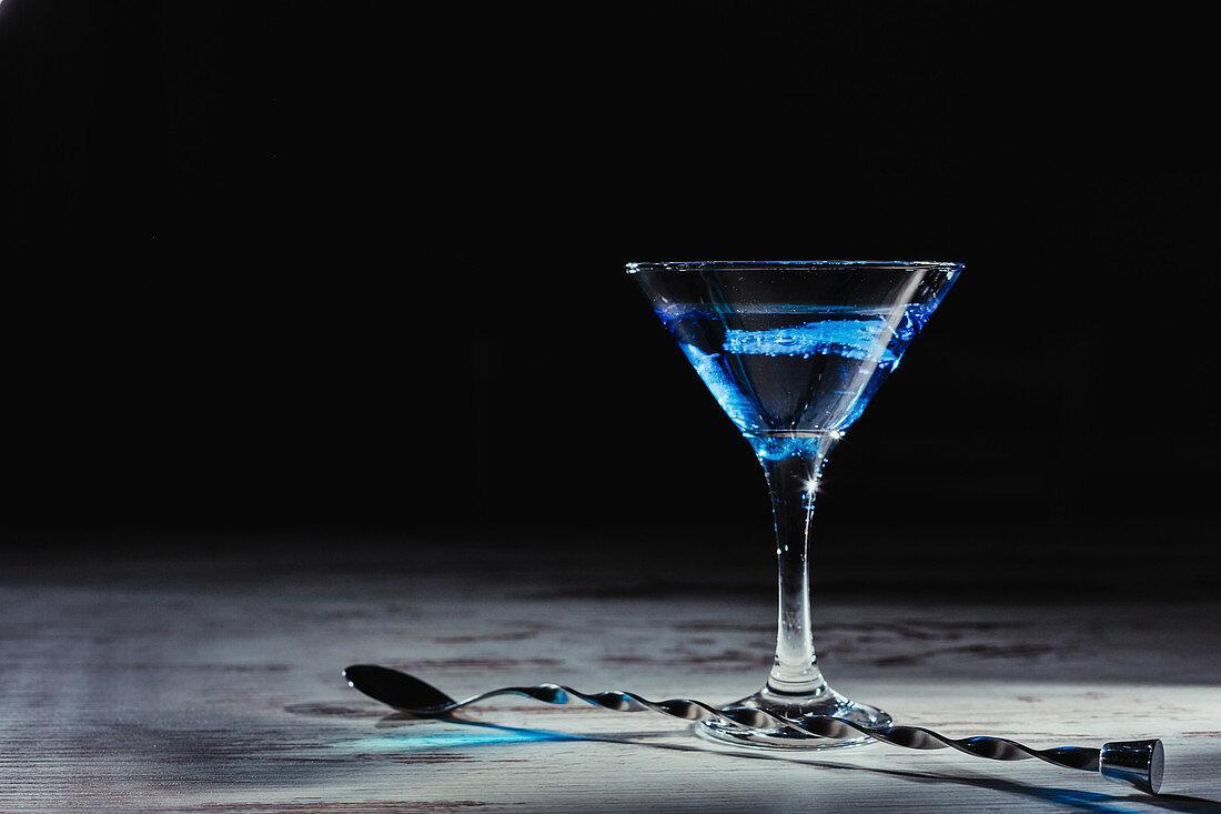 Blauer Cocktail im Stielglas neben gedrehtem Löffel