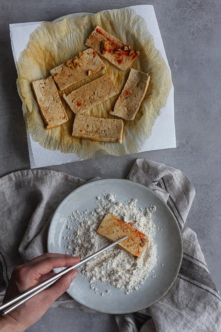 Marinierte Tofuscheiben mit Essstäbchen in Mehl wenden