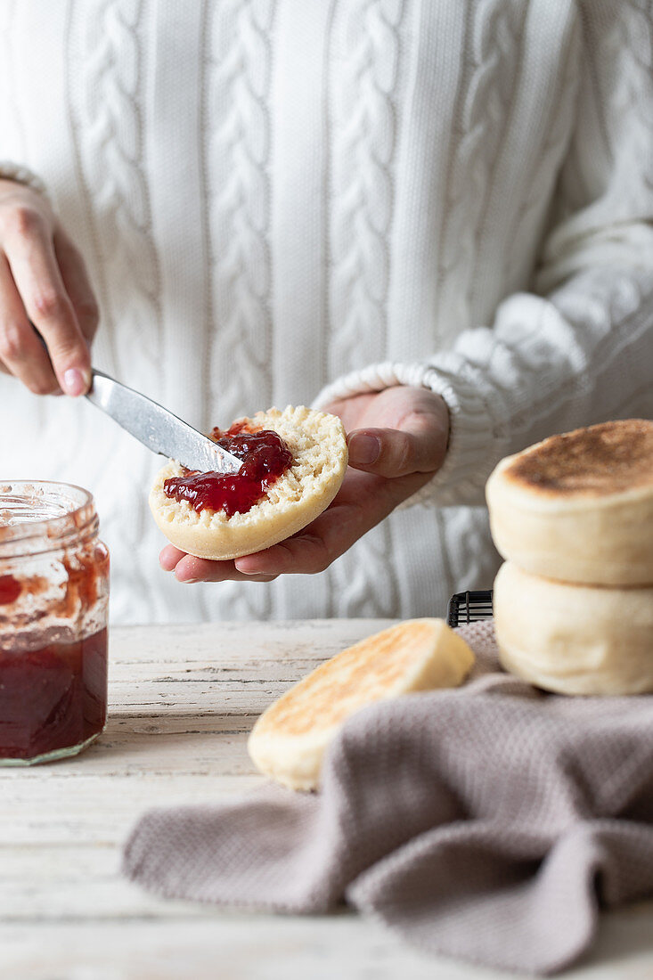Closeup of crop person spreading yummy red berry jam on cut fresh homemade bun