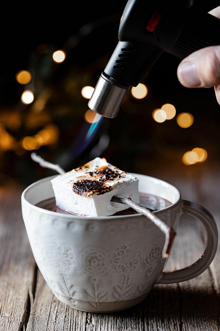 Marshmallow auf heisser Schokolade mit Gasbrenner anrösten