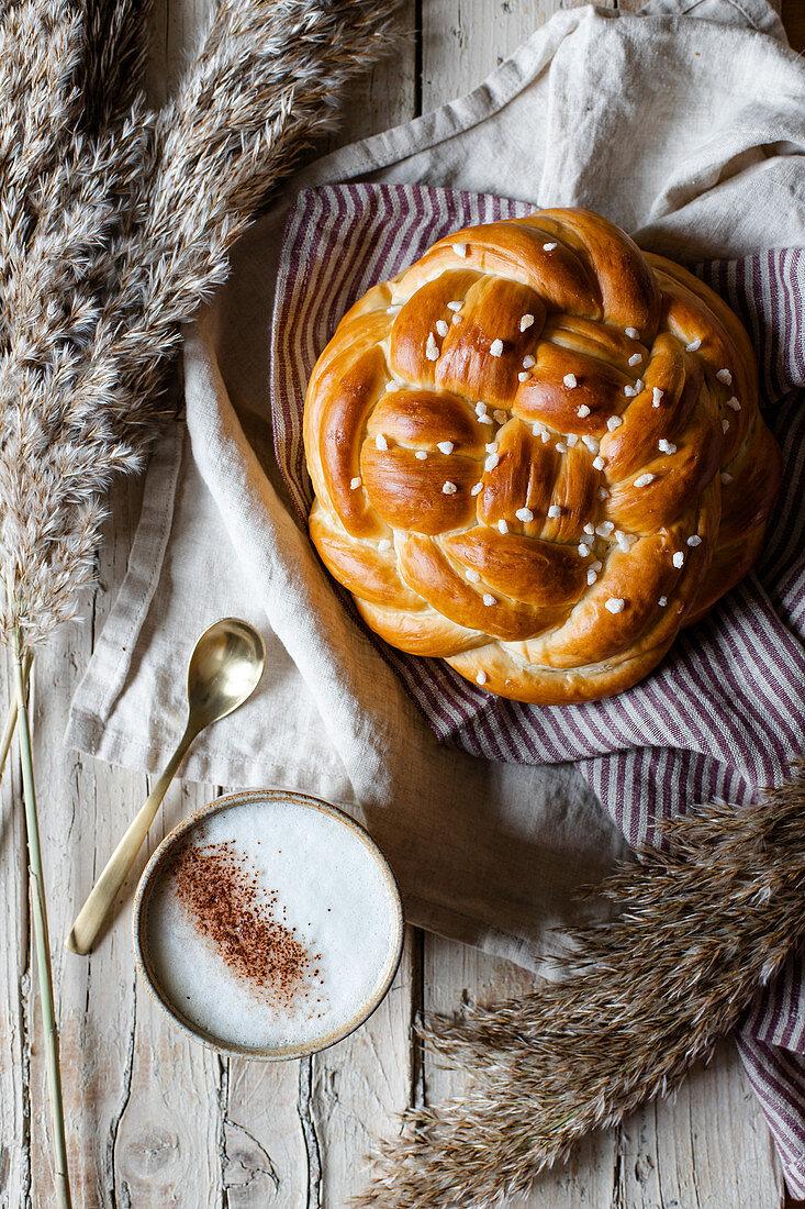 Tasse Cappuccino und geflochtenes Brot mit Hagelzucker
