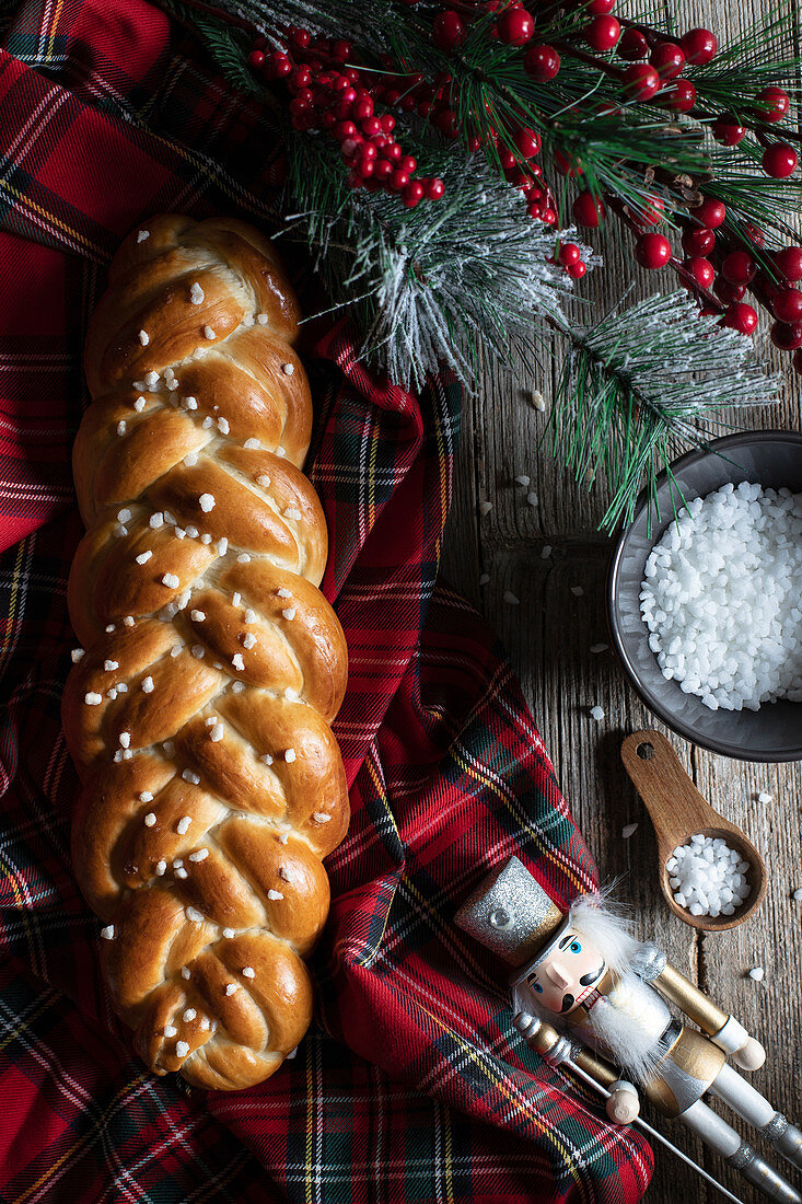 Traditional braided bread and knife placed on checkered Christmas tablecloth with decorative objects