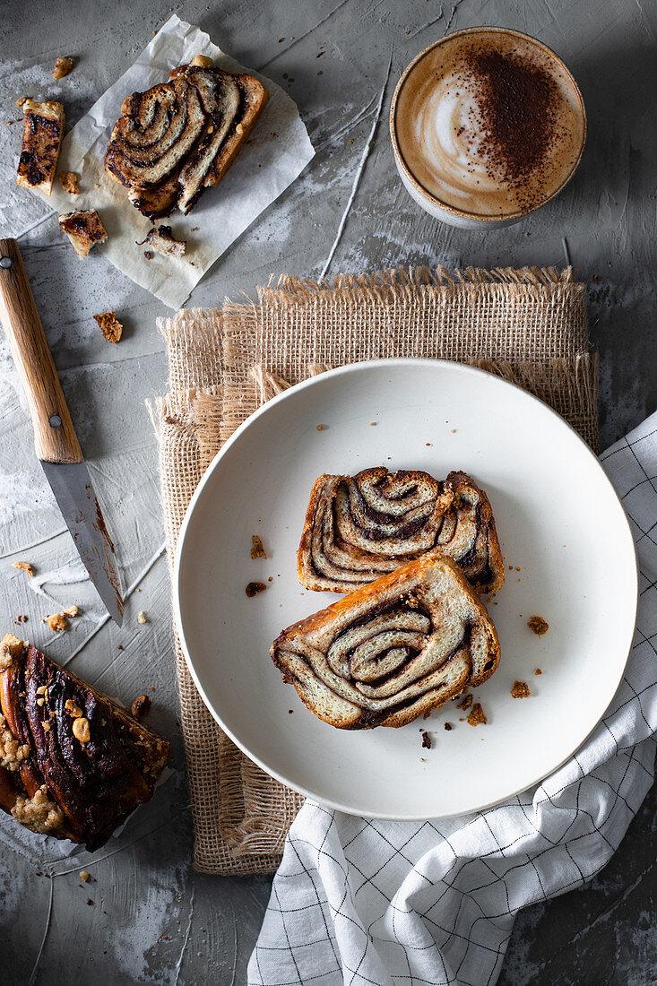 Hefekuchen mit Schokoladenfüllung, dazu Cappuccino