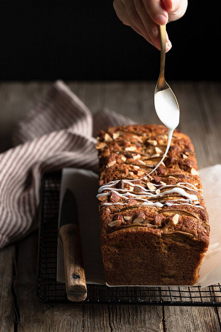 Pouring white sugar icing over homemade banana bread with nuts placed on metal grid on wooden table